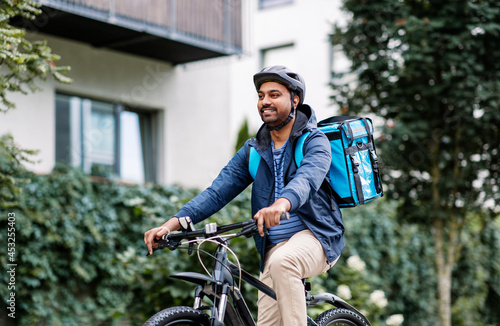 Fotografie, Obraz food shipping, profession and people concept - happy smiling indian delivery man