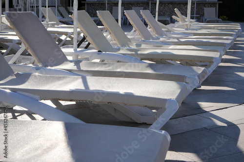 Fotografie, Tablou Empty sunbeds by the pool in the morning