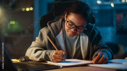 Photo Young Teenage Multiethnic Black Girl Writing Down Homework in a Notebook with a Pencil, Using Laptop Computer in a Dark Cozy Room at Home
