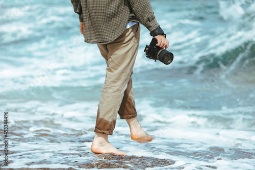 Fototapeta man holding professional came in hand walking by sea beach