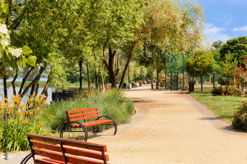 Tablou Canvas Wooden benches on the Dnipo embankment along the cobbled walking path of the city green park on a summer day