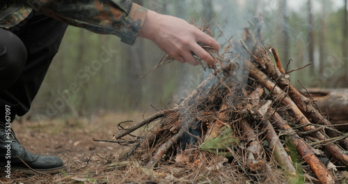 Fotografia Low angle shot of a man is trying make a fire in the forest