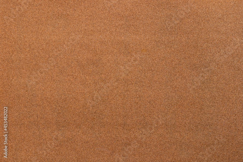 Fényképezés Sandpaper texture background where you can see the red-brown sand grain pattern on the sandpaper, suitable as a background for inserting text