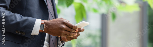 Valokuva cropped view of african american businessman in suit messaging on cellphone, ban