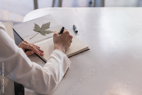 A businesswoman sits at her desk in her office and uses a pen to jot down appointments in her notebook as a reminder Fototapet