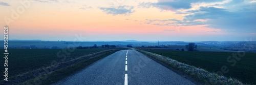 Valokuva An empty asphalt road (highway) through the fields at sunset