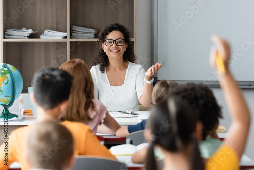Canvas Print positive african american teacher pointing at blurred girl raising hand in class
