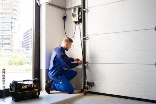 Fotografie, Tablou Garage Door Installation And Repair At Home. Contractor Man