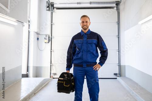 Fotografija Garage Door Installation And Repair At Home. Contractor Man