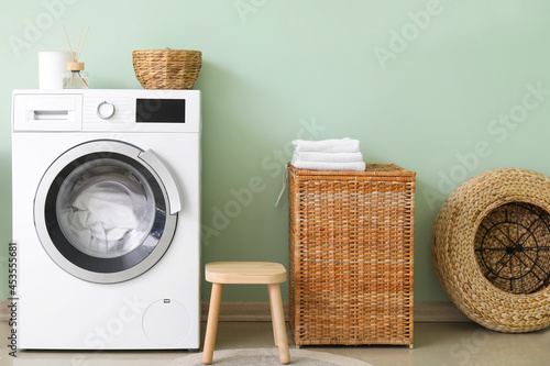 Obraz na plátně Modern washing machine with laundry in interior of bathroom