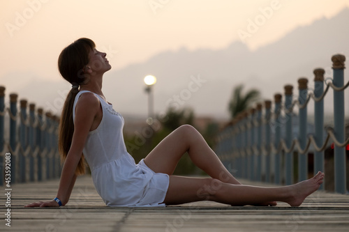 Young woman in light dress enjoying warm sunny evening on sea shore Fototapet