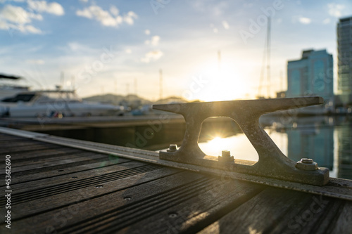 Slika na platnu Closeup of empty metal cleat on a yacht deck during sunset