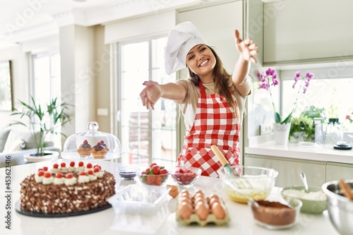 Fotografie, Obraz Beautiful young brunette pastry chef woman cooking pastries at the kitchen looking at the camera smiling with open arms for hug