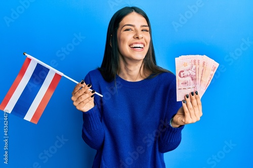 Fotografija Young hispanic woman holding thailand flag and baht banknotes smiling and laughing hard out loud because funny crazy joke