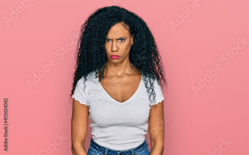 Fotografie, Obraz Middle age african american woman wearing casual white t shirt skeptic and nervous, frowning upset because of problem
