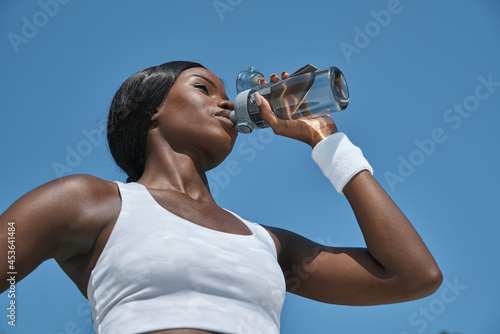 Low angle view of beautiful young African woman in sports clothing drinking wate Fototapet