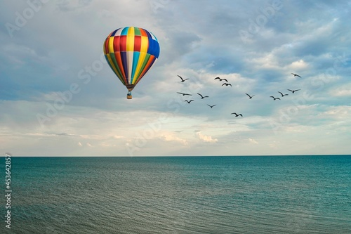 Fotografiet hot air balloon flies over the sea