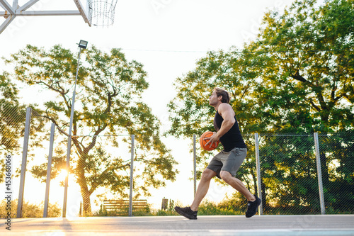 Foto Young side view sporty strong caucasian sportsman man wearing sports clothes training shooting free throw run playing with ball at basketball game playground court