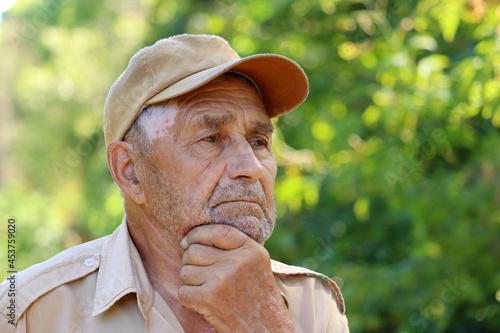 Fotografija Portrait of pensive elderly man on green nature background