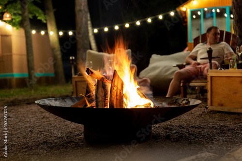 Canvas Print Cast iron fire pit campfire place at forest beach camping with brgiht burning flame at evening time against light bulb garland and trees