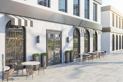 Murais de parede Contemporary concrete cafe exterior with terrace furniture in daylight