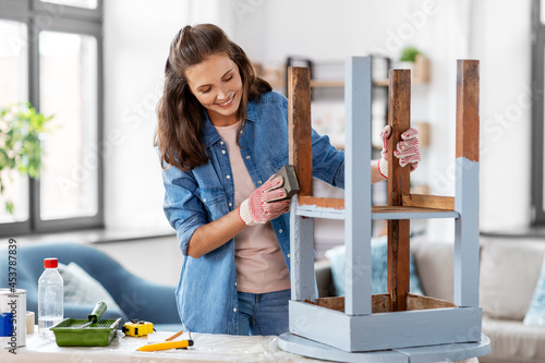 furniture renovation, diy and home improvement concept - happy smiling woman sanding old wooden table with sponge