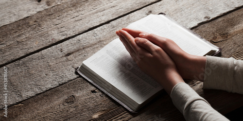 Woman hands praying with a bible in a dark over wooden table Fototapet
