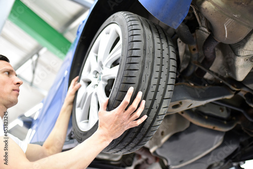 tyre change in a car repair shop - worker assembles rims on the vehicle Fototapet
