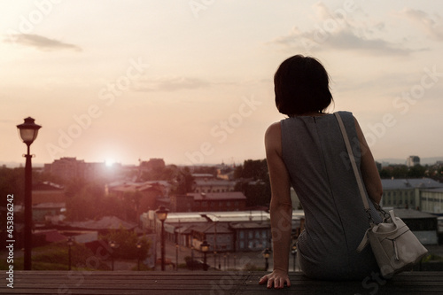 A lonely woman looks at the city at sunset from the observation deck rear view Fototapeta