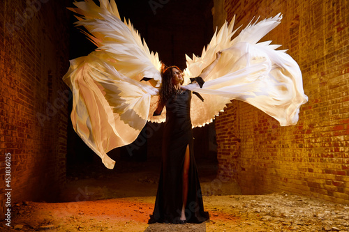 Canvastavla A brunette girl with long hair and white wings in an evening dress in a vintage Gothic castle