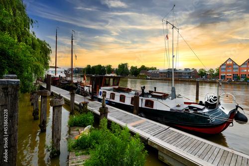 Fototapeta Idyllic river promenade with ships in Leer, East Frisia, Germany