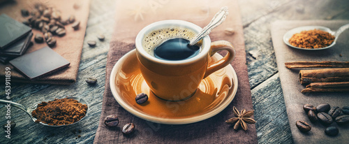Fotografía A cup of aromatic black coffee, a coffee maker, coffee beans of different varieties on the table