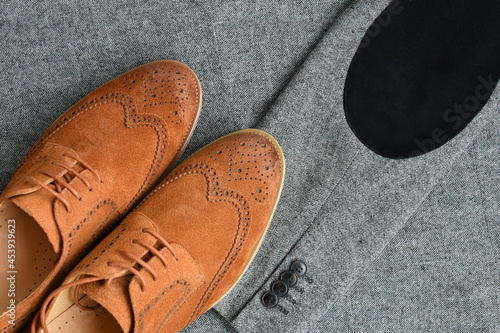 Fotografering A pair of brown suede derby shoes on tweed blazer background