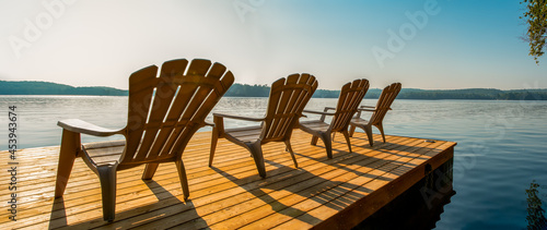 Fotografiet Row of Adirondack chairs -patio - deck chairs on wooden dock with sunset or sunrise -cottage life