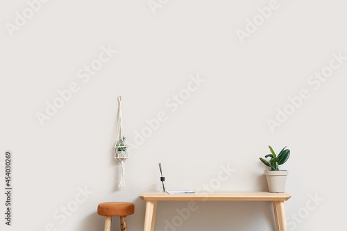 Foto Wooden TV stand with houseplants and chair near light wall