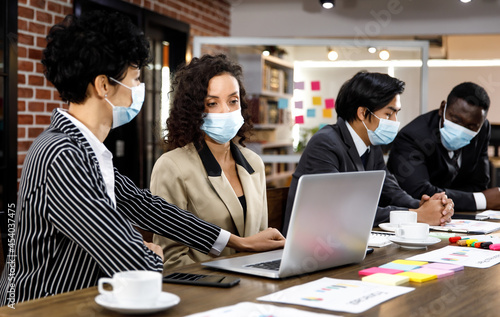 Multiracial mixed race businesspeople group working with concentration  at office, wearing face masks as new normal to protect or prevent virus in pandemic crisis, using laptop and job discussion Fotobehang