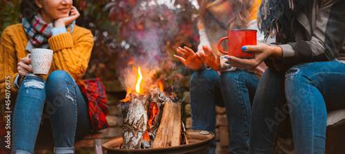 Photographie Three females best friends sitting around bonfire in casual clothes warming up a