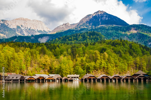 Picturesque landscape view of a row of boathouses on the famous Königssee lake on a cloudy day with the alps in the background in Schönau am Königssee in Bavaria, Germany Fototapete