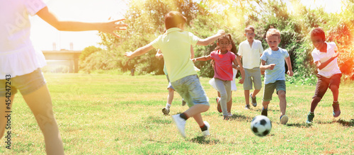 Fototapeta premium Group of happy kids are running and playing football in park at summer day