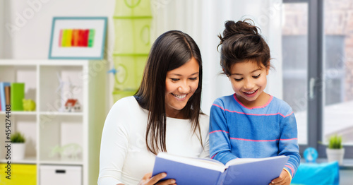 Photo family, education and school concept - happy mother and daughter reading book ov
