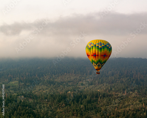 Fotografiet Hot air balloon in the cloudy sky over forests of Nappa Valley.