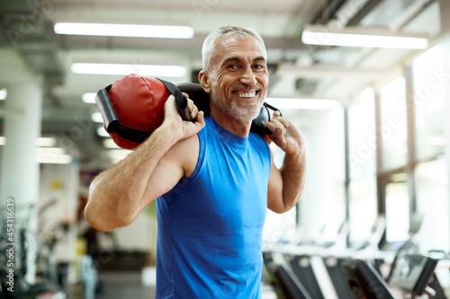 Fototapeta premium Happy mature sportsman exercises with sandbag during sports training at gym.