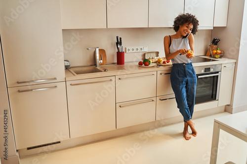 High-spirited woman peeling an apple during the phone call Fototapeta