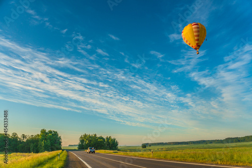 Fotografiet hot air balloon flying over the road
