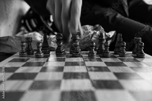 Murais de parede Grayscale closeup shot of a hand moving a piece on a chessboard