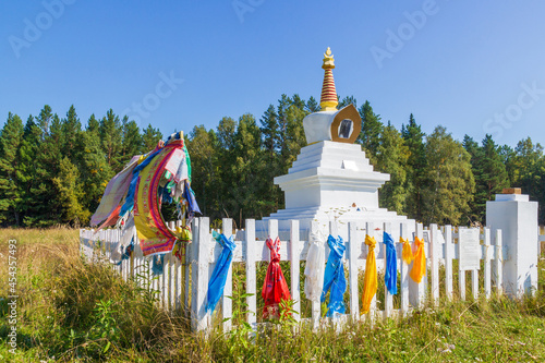 Obraz na płótnie White Buddhist Stupa of an Enlightenment decorated with colorful tibetan buddhist prayer scarves with traditional prayer texts in Sanskrit