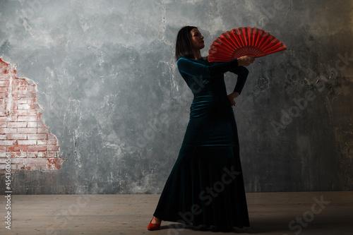 Young adult spanish woman dancing flamenco on gray vintage studio background Fotobehang