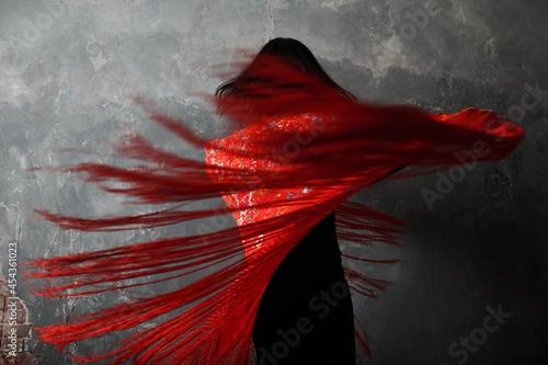 Fotografia Young adult spanish woman dancing flamenco on gray vintage studio background