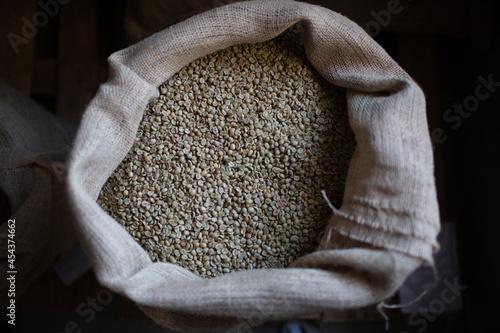 Stampa su Tela Green coffee beans in burlap sack at roaster company.