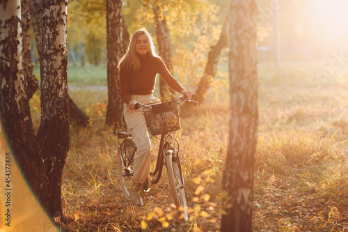 Foto Happy active young woman riding vintage bicycle in autumn park at sunset